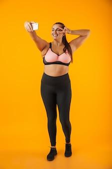 Retrato de corpo inteiro de uma jovem sorridente e gorda, vestindo roupas esportivas, isolada na parede amarela, tirando uma selfie