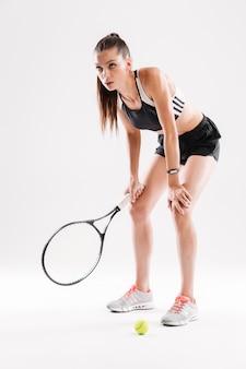 Retrato de corpo inteiro de uma jovem tenista exausta