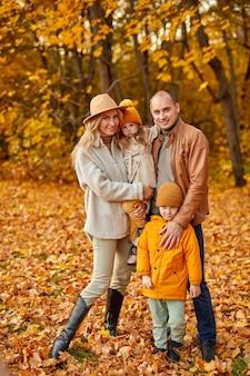 Retrato de corpo inteiro de uma linda família com filhos na floresta ensolarada de outono