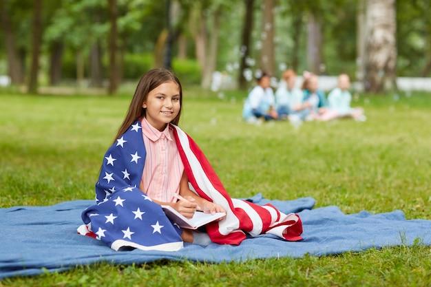 Retrato de corpo inteiro de uma linda garota coberta pela bandeira americana, sentado na manta de piquenique no parque e sorrindo