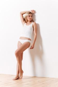 Retrato de corpo inteiro de uma linda garota magro em roupa interior