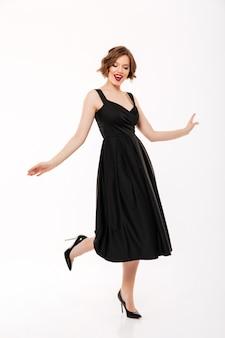 Retrato de corpo inteiro de uma linda garota vestida de vestido, apontando o dedo para uma caixa de presente em pé isolado sobre fundo rosa