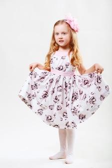 Retrato de corpo inteiro de uma linda garotinha loira dançando contra um fundo branco