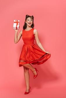 Retrato de corpo inteiro de uma linda jovem pin-up usando um vestido de pé isolado, mostrando uma caixa de presente