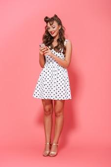 Retrato de corpo inteiro de uma linda jovem pin-up usando um vestido de pé isolado, usando um telefone celular