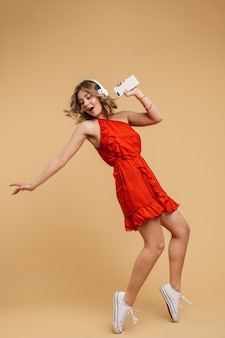 Retrato de corpo inteiro de uma linda jovem usando um vestido de pé isolado na parede amarela, ouvindo música com fones de ouvido, segurando um telefone celular, cantando