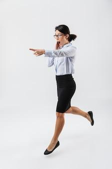 Retrato de corpo inteiro de uma linda mulher de negócios pulando isolada na parede branca, comemorando o sucesso, apontando para longe