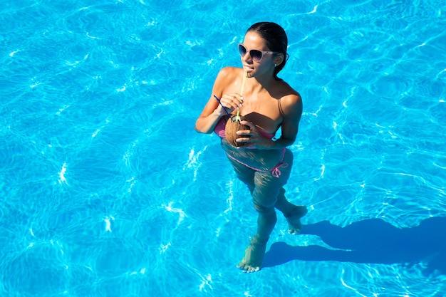 Retrato de corpo inteiro de uma linda mulher em pé na piscina e segurando coco com coquetel ao ar livre