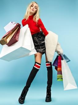 Retrato de corpo inteiro de uma linda mulher loira engraçada sorridente, andando com sacolas de compras coloridas isoladas sobre o fundo azul do estúdio. o conceito de estilo de vida, moda, venda e shopaholic