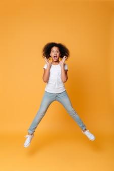 Retrato de corpo inteiro de uma menina africana animada pulando