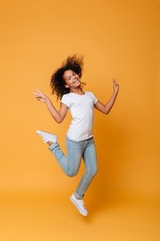Retrato de corpo inteiro de uma menina africana sorridente pulando