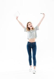 Retrato de corpo inteiro de uma menina alegre feliz segurando o bloco de notas