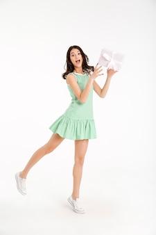 Retrato de corpo inteiro de uma menina alegre, vestida de vestido