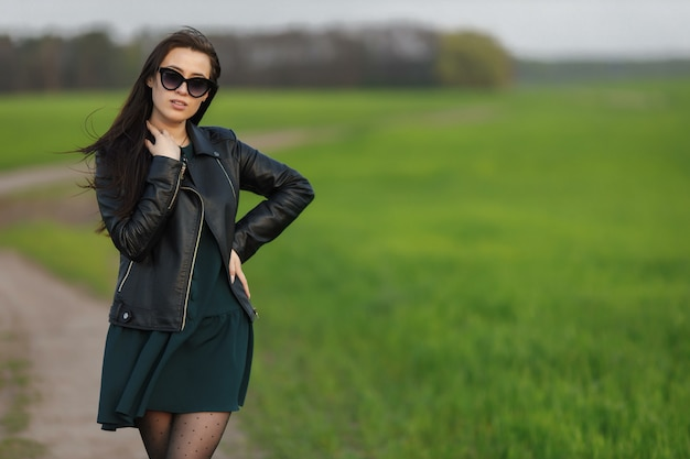Retrato de corpo inteiro de uma menina elegante andando ao longo de um campo verde. jovem sorridente está caminhando na natureza. prado verde primavera.