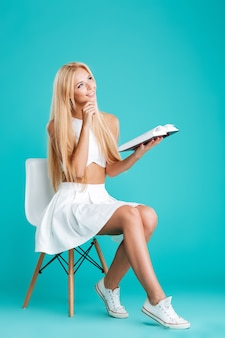 Retrato de corpo inteiro de uma menina encantadora sorridente com um livro pensando enquanto está sentado na cadeira, isolado no fundo azul