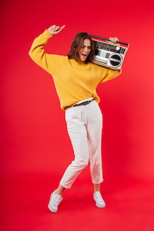 Retrato de corpo inteiro de uma menina feliz com um boombox