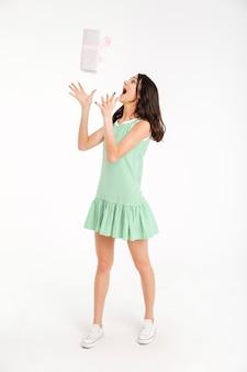 Retrato de corpo inteiro de uma menina feliz, vestida de vestido