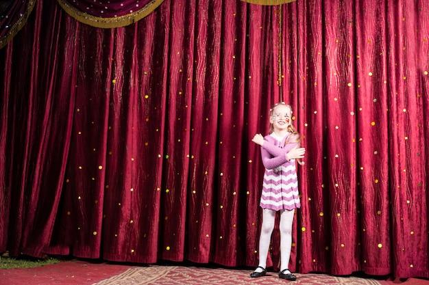 Retrato de corpo inteiro de uma menina loira sorridente usando maquiagem de palhaço e vestido listrado em pé no palco em frente à cortina vermelha