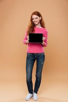 Retrato de corpo inteiro de uma menina ruiva bonita feliz, apontando o dedo para tablet digital