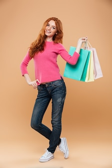 Retrato de corpo inteiro de uma menina ruiva bonita sorridente com sacolas de compras