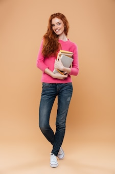 Retrato de corpo inteiro de uma menina ruiva bonita sorridente segurando livros