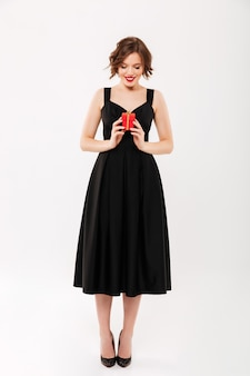 Retrato de corpo inteiro de uma menina sorridente, vestida de vestido preto