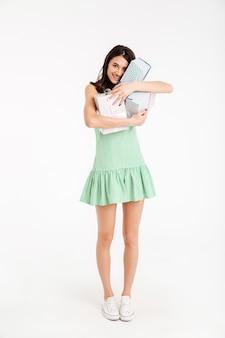 Retrato de corpo inteiro de uma menina sorridente, vestida de vestido