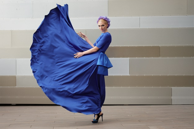 Retrato de corpo inteiro de uma moda mulher com seu vestido voando no ar