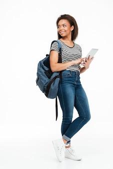 Retrato de corpo inteiro de uma mulher adolescente sorridente usando mochila
