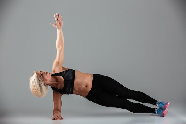 Retrato de corpo inteiro de uma mulher adulta muscular focada