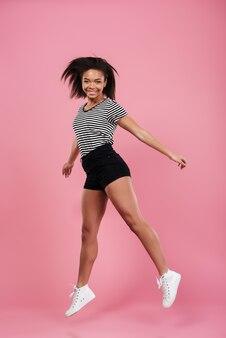 Retrato de corpo inteiro de uma mulher africana alegre e feliz pulando