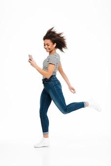 Retrato de corpo inteiro de uma mulher africana despreocupada feliz pulando