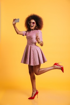 Retrato de corpo inteiro de uma mulher afro-americana alegre