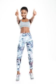 Retrato de corpo inteiro de uma mulher afro-americana esportiva, mostrando os polegares isolados em um fundo branco