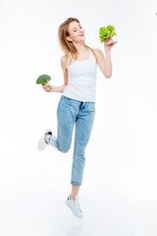 Retrato de corpo inteiro de uma mulher alegre, couve-flor e salada verde isolada em um fundo branco