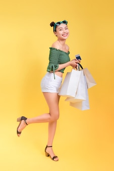 Retrato de corpo inteiro de uma mulher alegre e atraente segurando sacolas de compras e um cartão de crédito em fundo amarelo
