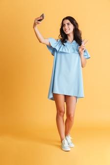Retrato de corpo inteiro de uma mulher alegre e sorridente em um vestido azul tirando uma selfie e mostrando o sinal da vitória isolado