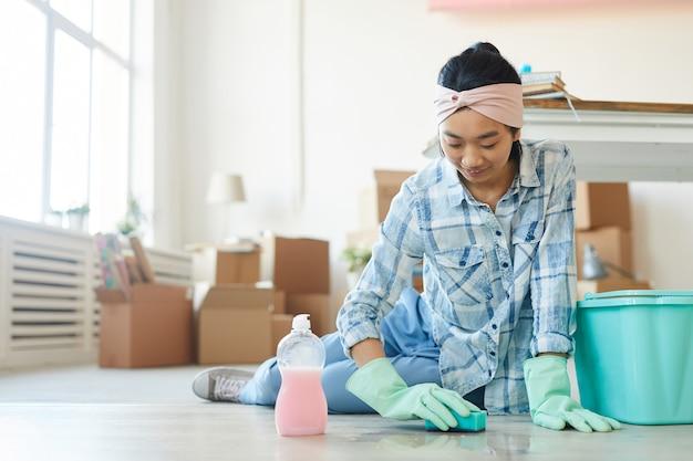 Retrato de corpo inteiro de uma mulher asiática feliz limpando o chão de uma casa ou apartamento novo depois de se mudar