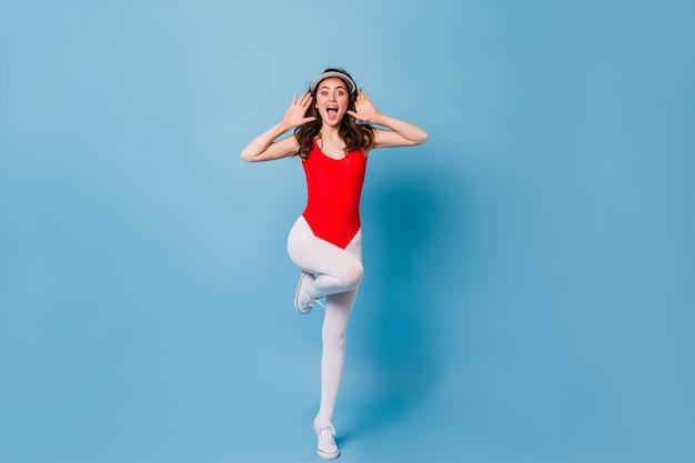 Retrato de corpo inteiro de uma mulher ativa em um body esportivo e leggings