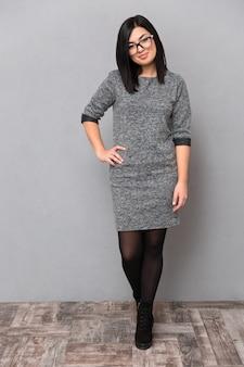 Retrato de corpo inteiro de uma mulher atraente com vestido e óculos em pé na parede cinza