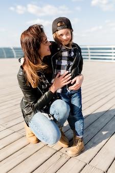 Retrato de corpo inteiro de uma mulher bonita com uma filha pequena, vestindo roupas semelhantes, posando ao ar livre sob a luz do sol