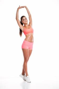 Retrato de corpo inteiro de uma mulher bonita de aptidão esticando as mãos