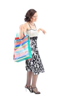 Retrato de corpo inteiro de uma mulher bonita e feliz com sacolas de compras coloridas nas mãos