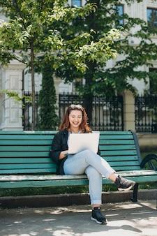 Retrato de corpo inteiro de uma mulher bonita plus size sentada em um banco com um laptop nas pernas, olhando para o laptop sorrindo contra um edifício.