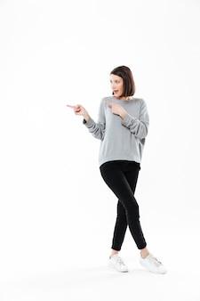 Retrato de corpo inteiro de uma mulher casual, apontando dois dedos