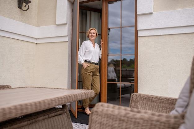 Retrato de corpo inteiro de uma mulher caucasiana loira elegante, sorridente, atraente, esguia, parada na porta de uma casa particular