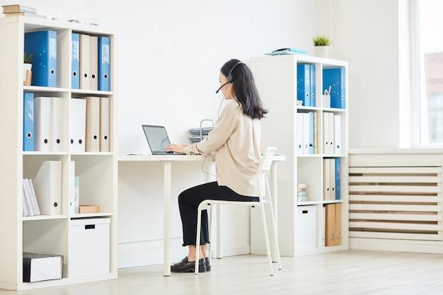 Retrato de corpo inteiro de uma mulher de negócios moderna usando fone de ouvido enquanto trabalha em casa