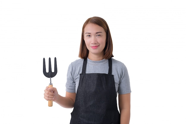Retrato de corpo inteiro de uma mulher de trabalhador ou servicewoman na camisa cinza e avental está segurando a pá para cultivadores em fundo branco