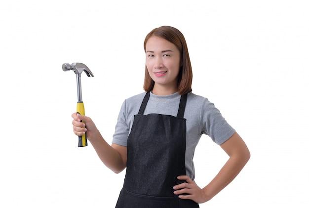 Retrato de corpo inteiro de uma mulher de trabalhador ou servicewoman na camisa cinza e avental está segurando o martelo isolado no fundo branco