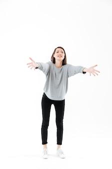 Retrato de corpo inteiro de uma mulher em pé com as mãos estendidas